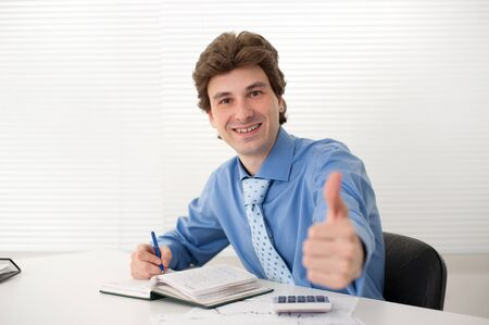 businessman showing thumbs up gesture in the office photo