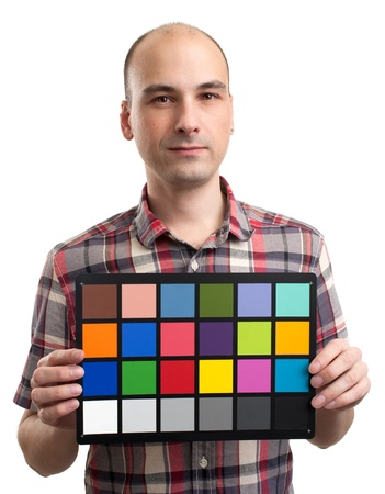 man holds an white balance card with test colors Stock Photo - 17054568