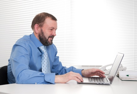 Portrait of a senior business man sitting by his laptop in the office Stock Photo - 17850241