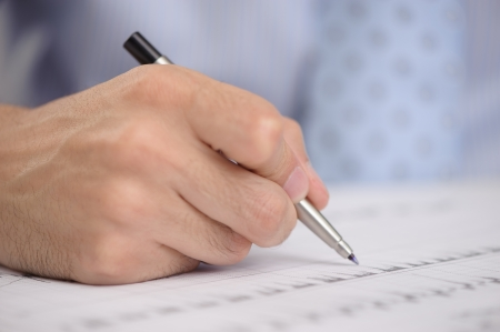 Close-up of business person hand with pen photo