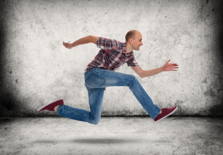 Man running. Gray concrete wall and floor photo
