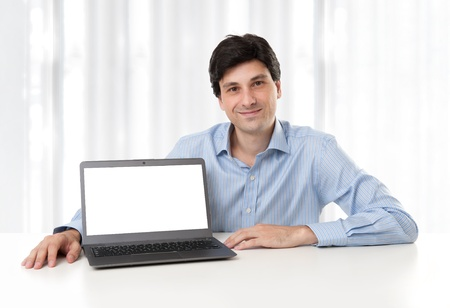 handsome young businessman displaying laptop with blank screen photo