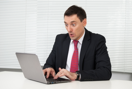 shocked young business man looking on his laptop computer photo