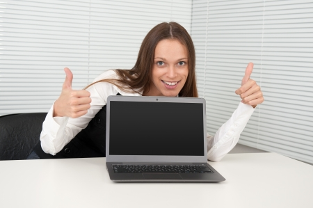 Cheerful businesswoman showing thumbs up in front of laptop photo