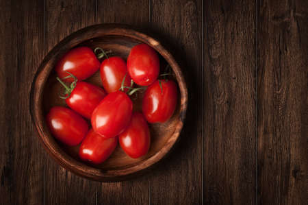 Tomatoes on the grunge wooden background