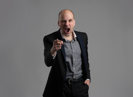 Angry man pointing his finger against somebody and screaming photo