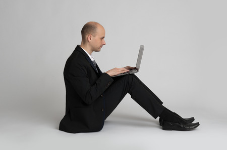 seated young businessman using a laptop photo
