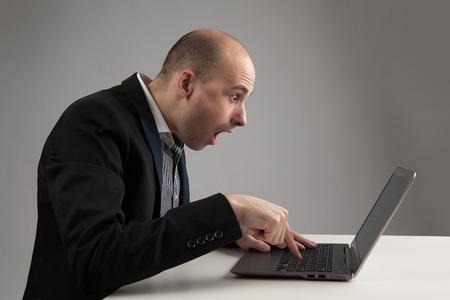 bald man: hombre de negocios sorprendió mirando a su ordenador portátil