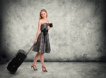 Full body portrait of young female in dress standing with her travel bag photo