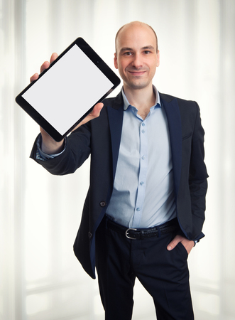 Smiling man holding a tablet with blank screen photo