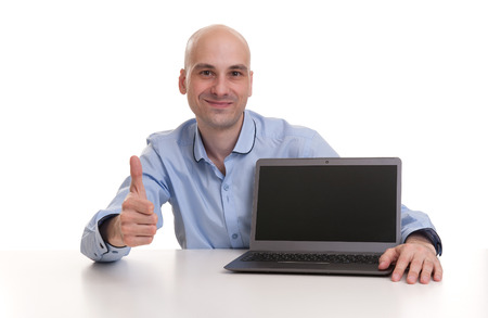bald Man showing his thumb up and laptop with blank screen photo