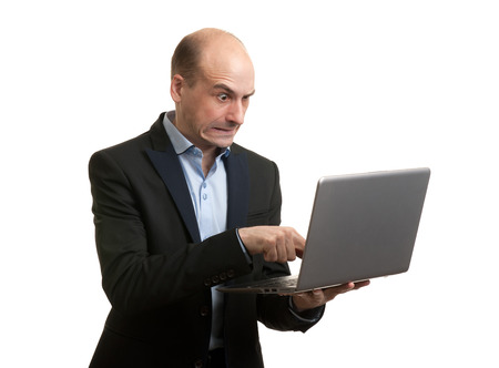Angry businessman with laptop computer. Isolated over white photo