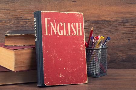 Englisch lernen Konzept. Buch auf einem hölzernen Hintergrund
