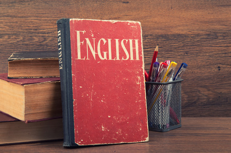 learning english concept. book on a wooden background Imagens