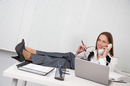 legs up: young business woman talking on phone in office