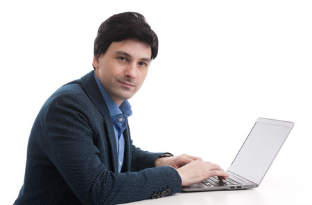 businessman working at his computer: businessman working on his laptop computer. Isolated over white