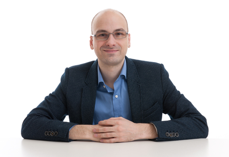 people sitting: handsome bald man sitting at the desk isolated over white Stock Photo