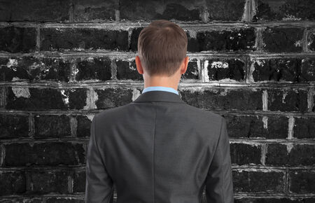 impasse: Back view of Businessman looking at brick wall Stock Photo