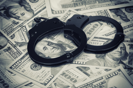 US dollars. Handcuffs on money close up photo