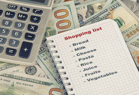 checking ingredients: close up of shopping list and money