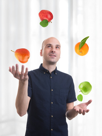 juggle: man juggle fruits. Apple, orange and pear