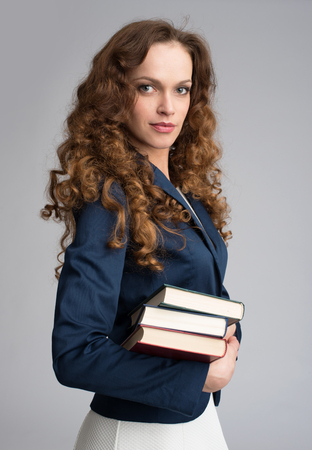 grijze achtergrond: Smiling business woman holding stack of books. Gray background Stockfoto