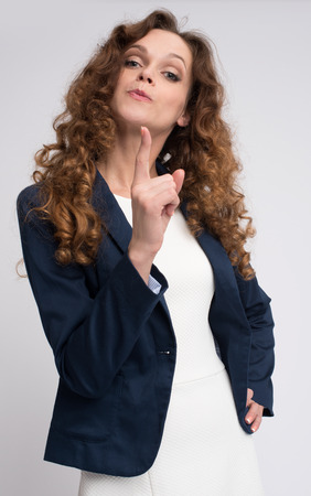 threatening: serious young woman threatening with finger. Isolated over gray Stock Photo