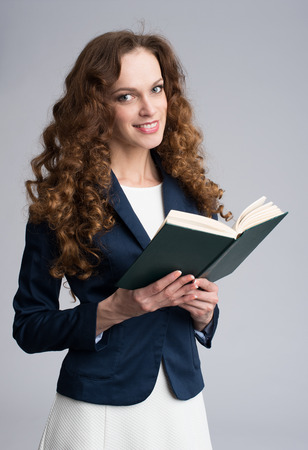 grijze achtergrond: Young woman with a book over gray background Stockfoto