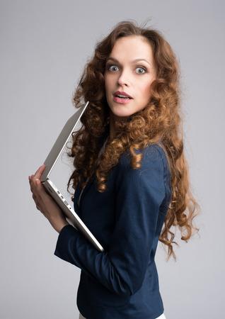 astonishment: Mujer asombro con el port�til. Aislado en el fondo gris Foto de archivo