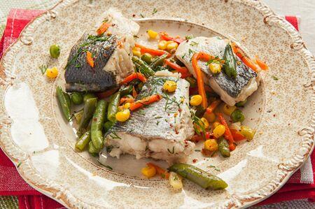 pesce cotto: pesce cucinato con verdure su un piatto