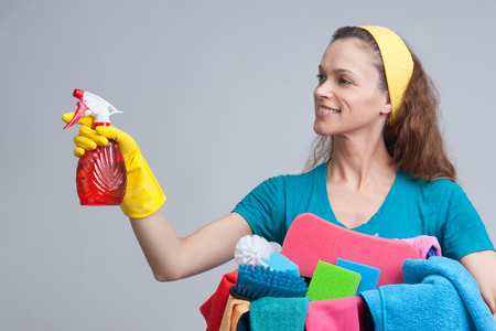 charwoman: Beautiful cheerful woman holding different cleaning stuff. Isolated Stock Photo