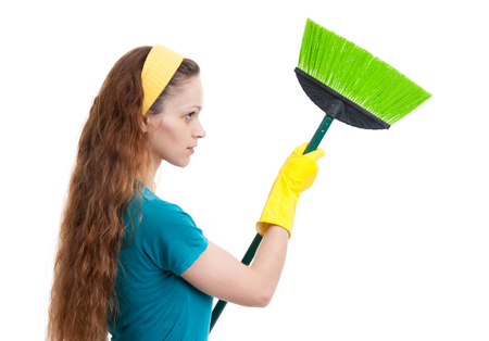 spring cleaning: woman with broom isolated on a white background