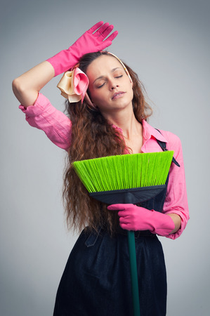 housewife gloves: woman cleaning wearing pink rubber gloves. Tired housewife with broom