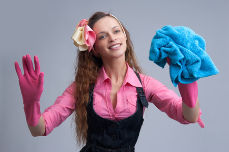 Laughing woman wiping with a blue rag wearing rubber gloves Stock Photo
