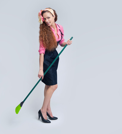 charwoman: woman cleaning with broom. Cleaning service concept
