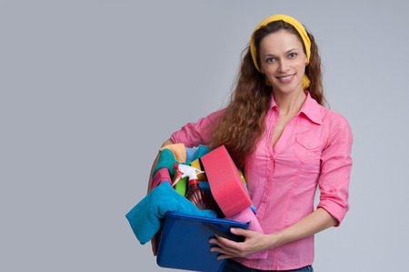 charlady: Beautiful cheerful woman holding different cleaning stuff. Isolated Stock Photo