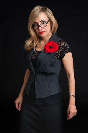 feminity: woman wearing glasses and a jacket looking at the camera with a serious expression