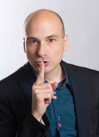 shh: bald man with a gesture of shh on gray background