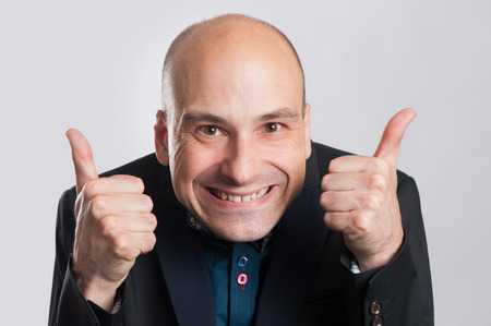 exaggerated: bald man making a silly face and giving thumb up. Isolated on gray.