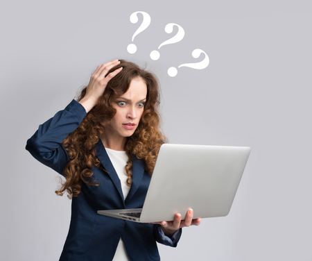 computer isolated: Young woman having trouble with laptop. Gray background Stock Photo