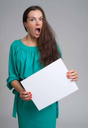 grijze achtergrond: surprised woman holding blank sign over gray background Stockfoto