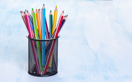 back to school supplies: Colour pencils in a black mug on blue background