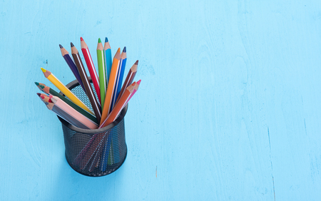 back to school supplies: close up of colorful pencils on blue background