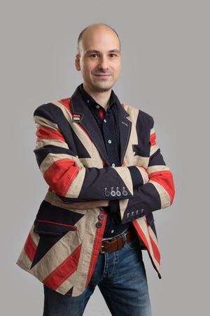 englishman: handsome bald man wearing fashionable jacket. Studio shot