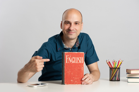 learning english: bald man sits at the desk and learning English Stock Photo