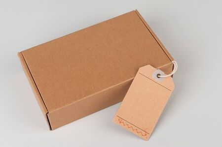 label tag: parcel. cardboard box with blank tag isolated on grey background Stock Photo