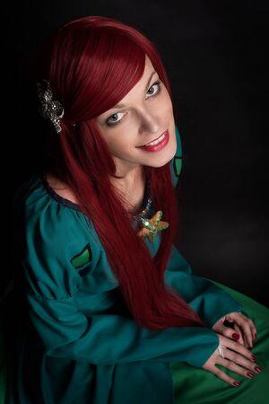 ooking: Beautiful redhead Girl. Caucasian woman low key portait over dark background