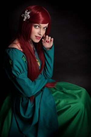 Beautiful redhead Girl. Caucasian woman low key portait over dark background