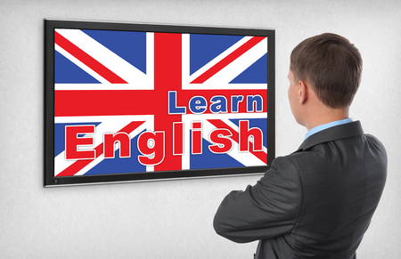 Learning english concept. Business man looking on a monitor screen photo