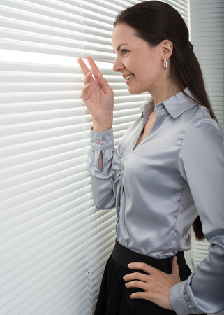 window blinds: smiling business woman looking through window blinds Stock Photo